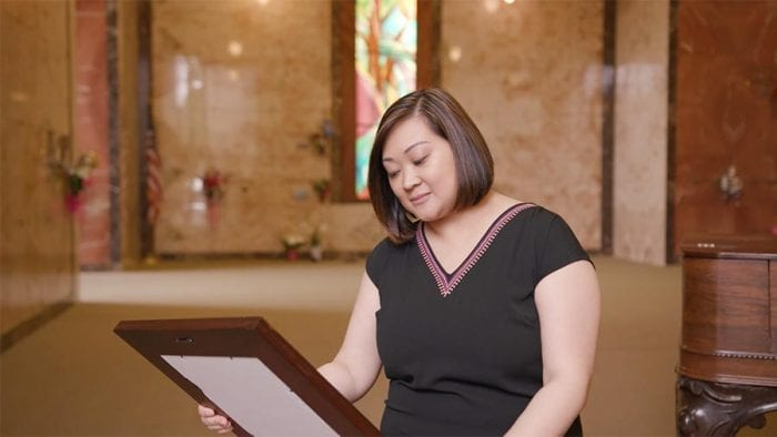 A woman in mausoleum looks down lovingly at framed photo of deceased loved one