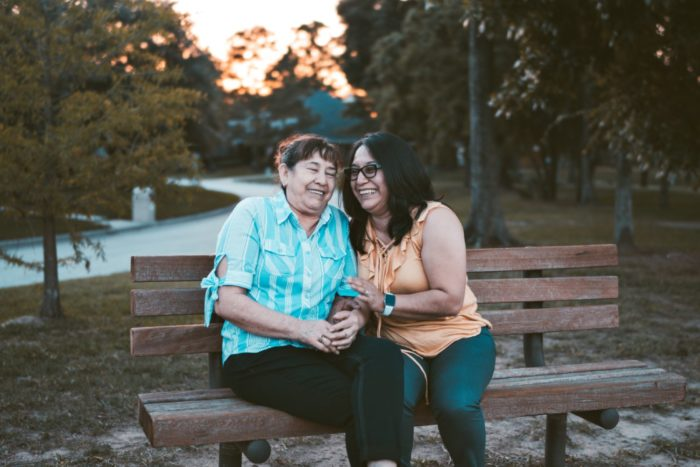 Mother and daughter laugh on park bench