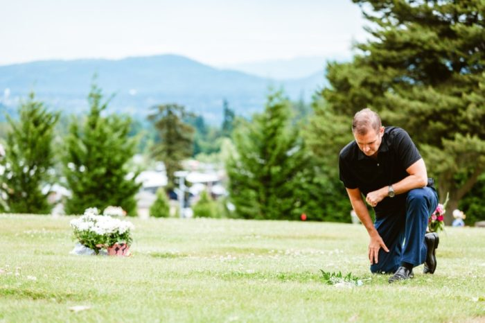 Man kneels alone at grave in Washington Memorial cemetery
